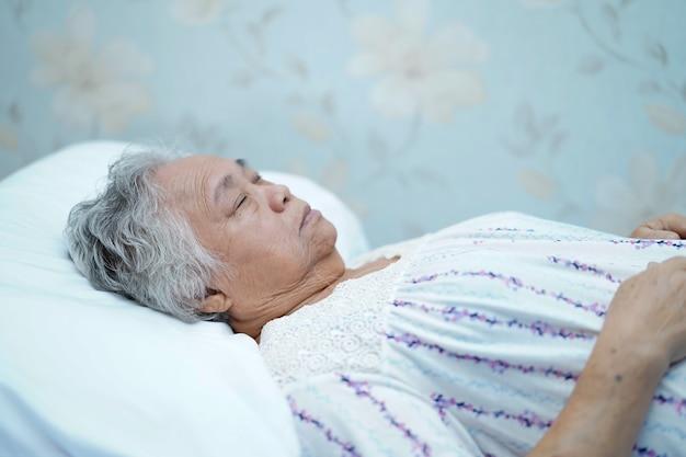 Aziatische hogere of bejaarde oude dame die van de damepatiënt op bed in het pleegziekenhuis liggen.