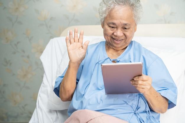 Aziatische hogere of bejaarde oude damevrouw die digitale tablet voor videogesprek gebruiken; sociaal afstandsconcept.