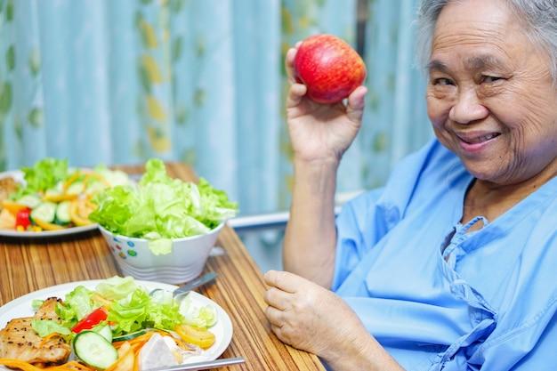 Aziatische hogere of bejaarde oude damevrouw die geduldig ontbijt gezond voedsel eet
