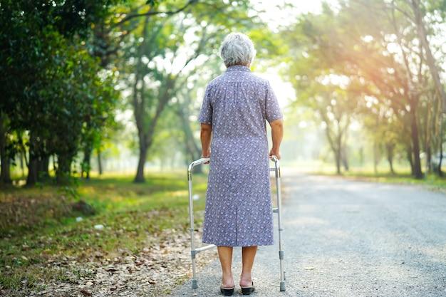Aziatische hogere of bejaarde oude damevrouw geduldige gang met leurder in park.