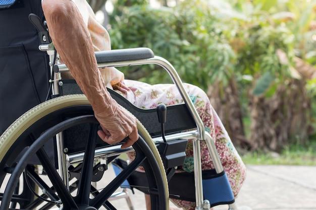 Aziatische hogere of bejaarde oude damevrouwenpatiënt op rolstoel bij het voorhuis