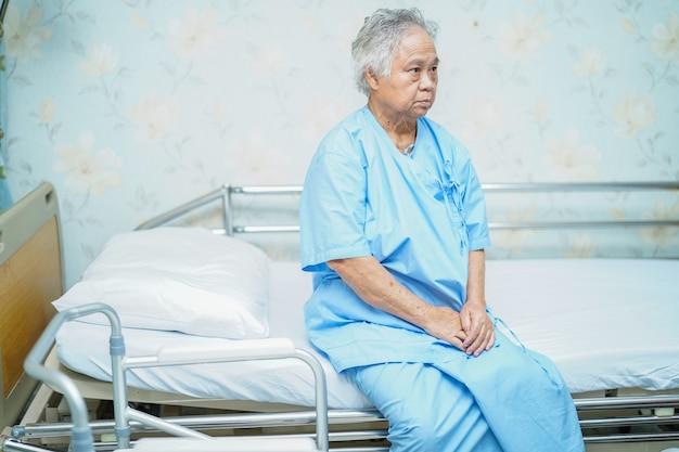 Aziatische hogere of bejaarde oude geduldige zitting van de damevrouw op bed in de verpleegafdeling van het verpleegingsziekenhuis met hoop en wachtend haar verwant: gezond sterk medisch concept.