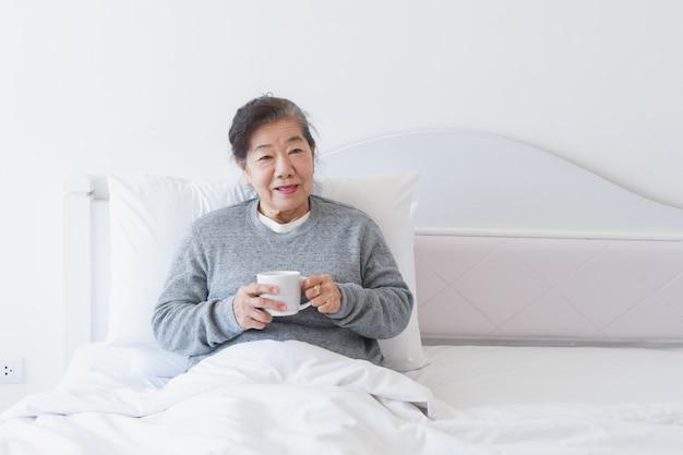 Aziatische hogere oude vrouw het drinken koffie of thee op het bed