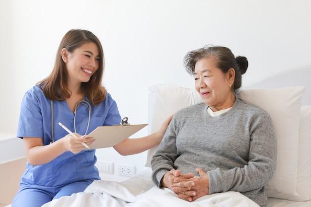 Aziatische hogere oude vrouw op het bed met arts en haar zoon in het ziekenhuis