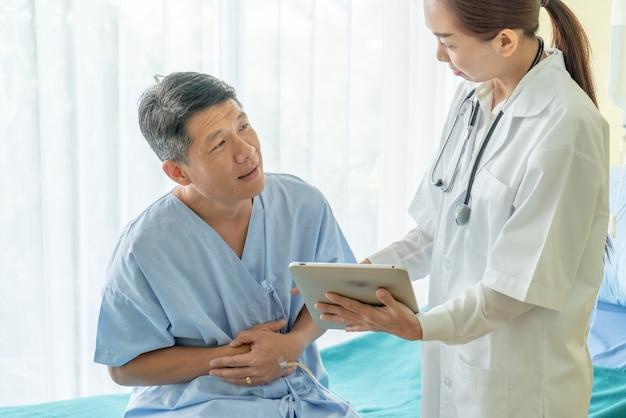 Aziatische hogere patiënt die op het ziekenhuisbed met vrouwelijke arts bespreken