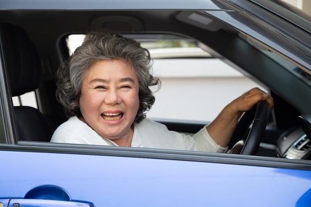 Aziatische hogere vrouw die een auto drijven en gelukkig met blije positieve uitdrukking glimlachen tijdens de aandrijving om reis te reizen, genieten de mensen van lachend vervoer en aandrijving door concept