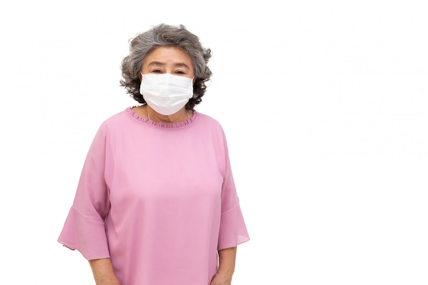 Aziatische hogere vrouw die een beschermend gezichtsmasker voor besmettelijke ziekte covid-19 draagt die op witte muur wordt geïsoleerd. hygiënisch gezichtsmasker voor veiligheid buiten milieubewustzijn of virusverspreiding concept