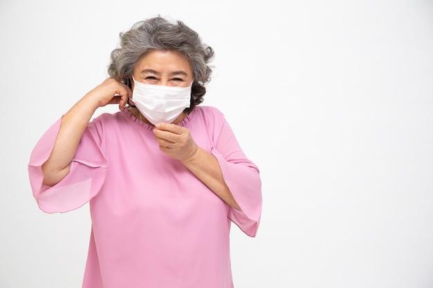 Aziatische hogere vrouw die een beschermend gezichtsmasker voor pestcoronavirus of covid-19 besmettelijke ziekte draagt. hygiënisch gezichtsmasker voor veiligheid buiten milieubewustzijn of virusverspreiding concept