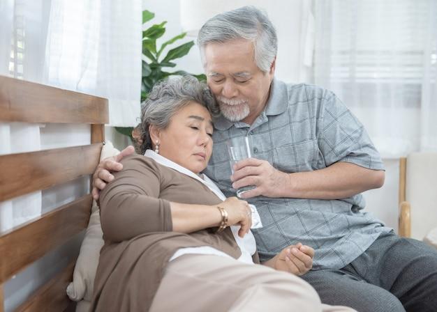Aziatische hogere vrouw die geneesmiddelen en drinkwater nemen terwijl het zitten op laag. oude man zorgt voor zijn vrouw terwijl haar ziekte thuis. gezondheidszorg en geneeskunde concept.