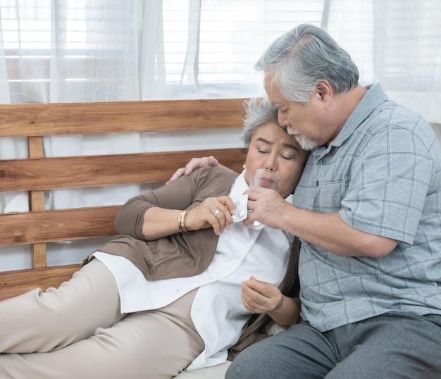 Aziatische hogere vrouw die geneesmiddelen en drinkwater nemen terwijl het zitten op laag. oude man zorgt voor zijn vrouw terwijl ze ziek is in huis.
