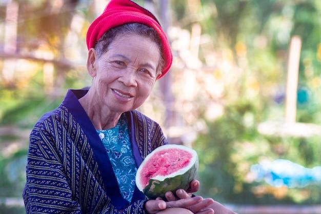 Aziatische hogere vrouw die watermeloen met glimlach eet en gelukkig