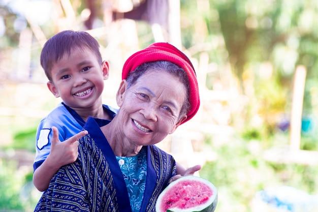 Aziatische hogere vrouw en haar kleinzoon die watermeloen met glimlach eten en gelukkig