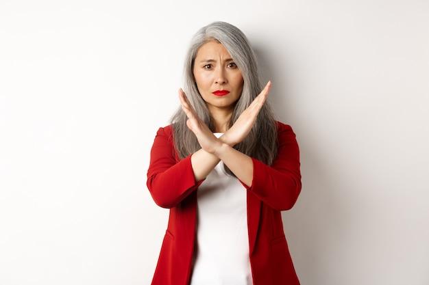 Aziatische hogere vrouw in rode blazer die dwarsgebaar maakt, u smeekt te stoppen, het niet eens bent en iets afkeurt, staande op een witte achtergrond.