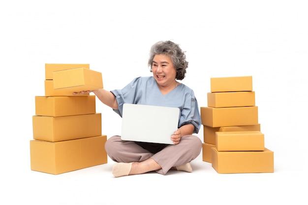 Aziatische hogere vrouw start klein bedrijf freelance met pakketdoos en computer.