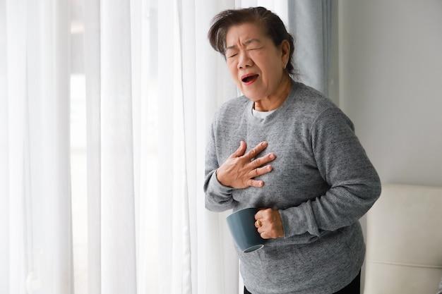 Aziatische hogere vrouwenmoeder ziek met hart attact in woonkamer