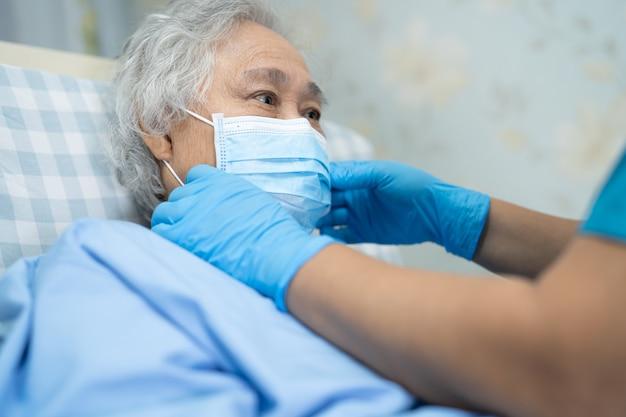 Aziatische hogere vrouwenpatiënt die een gezicht draagt om covid-19 coronavirus te beschermen.