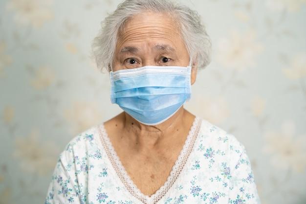 Aziatische hogere vrouwenpatiënt die een gezichtsmasker draagt ter bescherming van het coronavirus