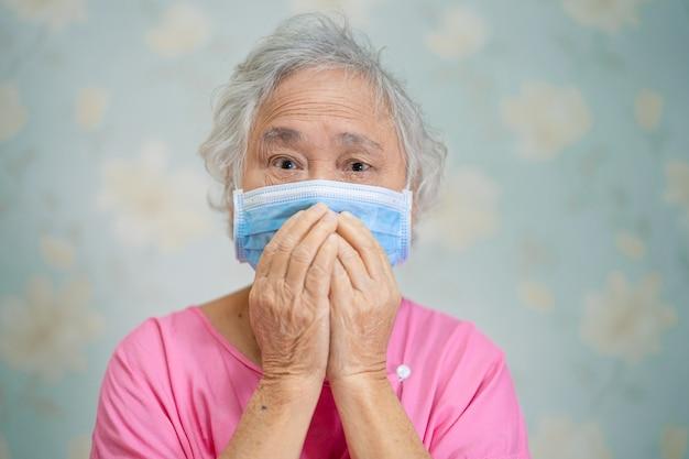 Aziatische hogere vrouwenpatiënt die een gezichtsmasker draagt ter bescherming van het covid-19 coronavirus.