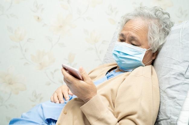 Aziatische hogere vrouwenpatiënt die mobiele telefoon in het ziekenhuis houdt ter bescherming van covid-19 coronavirus.