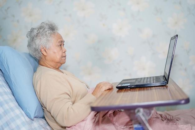 Aziatische hogere vrouwenpatiënt die notitieboekjecomputer met behulp van.