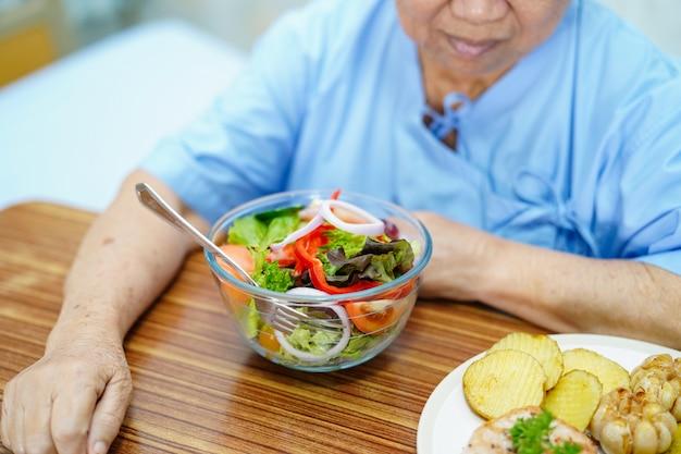 Aziatische hogere vrouwenpatiënt die ontbijt in het ziekenhuis eten.