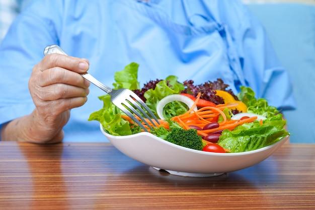 Aziatische hogere vrouwenpatiënt die ontbijt op bed in het ziekenhuis eten.