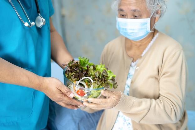 Aziatische hogere vrouwenpatiënt die ontbijtgroente eten in het ziekenhuis.
