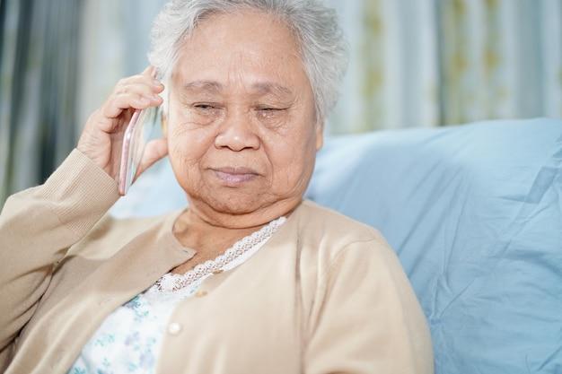 Aziatische hogere vrouwenpatiënt die op de mobiele telefoon in het ziekenhuis spreekt.