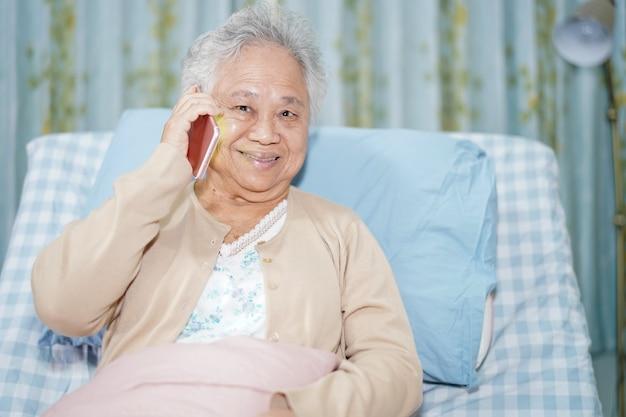 Aziatische hogere vrouwenpatiënt die op de mobiele telefoon spreken terwijl het zitten op bed in het ziekenhuis.
