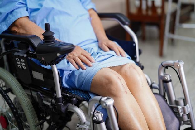 Aziatische hogere vrouwenpatiënt op elektrische rolstoel met afstandsbediening.