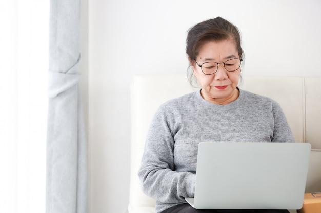 Aziatische hogere vrouwenpensionering die laptop computer in woonkamer met behulp van