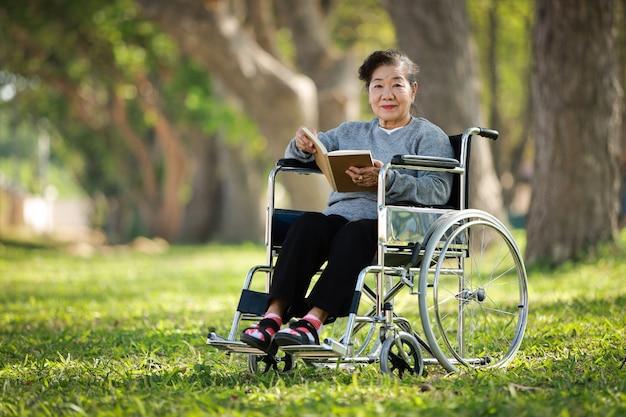 Aziatische hogere vrouwenzitting op de rolstoel en het lezingsboek in de glimlach van het parktuin en het gelukkige gezicht
