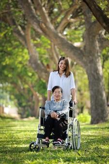Aziatische hogere vrouwenzitting op de rolstoel met haar gelukkig de glimlachgezicht van de dochterfamilie op het groene park