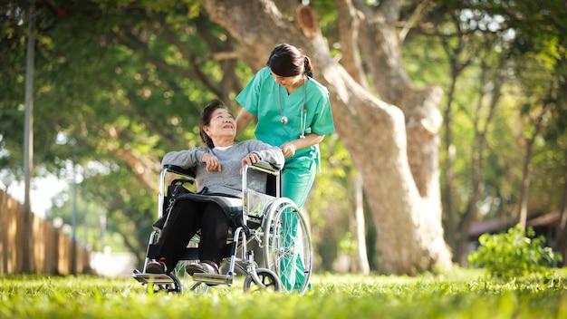 Aziatische hogere vrouwenzitting op de rolstoel met vrouw in arts eenvormig in het parkziekenhuis