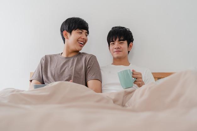 Aziatische homoseksuele mannen koppelen praten met een geweldige tijd in een modern huis. jonge de minnaar mannelijke gelukkig van azië ontspant rust drinkt koffie na kielzog omhoog terwijl het liggen op bed in slaapkamer bij huis in de ochtend.