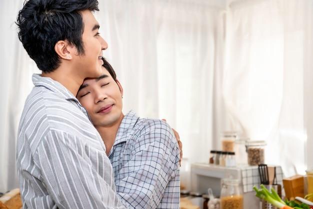 Aziatische homoseksuele paaromhelzing en kus bij keuken in de ochtend