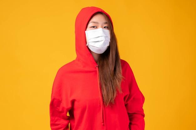 Aziatische hoodies meisje met beschermend gezichtsmasker voor bescherming tijdens de quarantaine coronavirus covid19 uitbraak op gele achtergrond, beschermen verspreiding covid-19 en pm2.5 luchtvervuiling