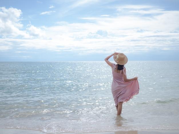 Aziatische huid tan vrouw met roze jurk en hoed staande ontspannen op zandstrand met onscherpte beeld van zee. voor reizen zomer in vakanties.