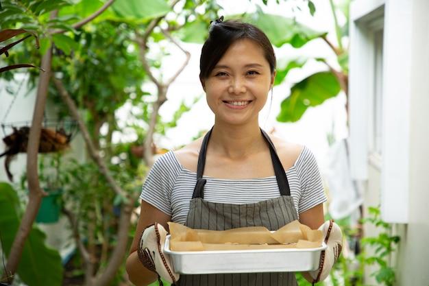Aziatische huishoudster vrouw met brownies lade. zelfgemaakt eten