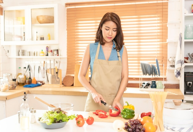 Aziatische huisvrouw bereidt voedselsalade thuis in de keukenkamer.