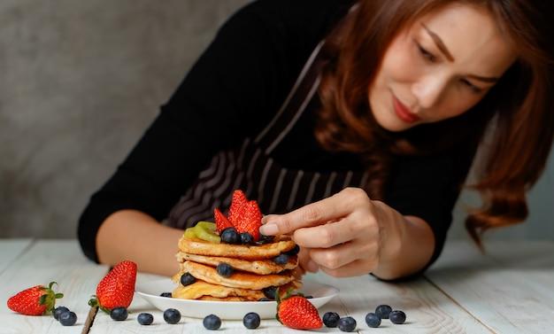 Aziatische huisvrouw bereidt zelfgemaakte pannenkoeken voor familie, topping, aardbeien, bosbessen en kiwi bovenop met blij en concentraat.