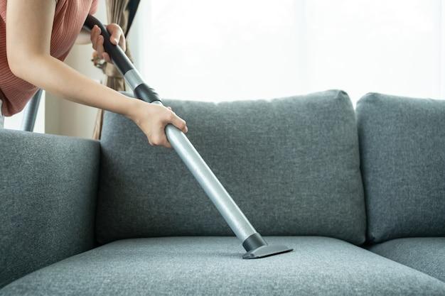 Aziatische huisvrouw die een draadloze vacuümmachine gebruikt om een bank in de woonkamer van dichtbij schoon te maken. aziatische huishoudster stofzuigen in de woonkamer. klusjes en dagelijkse huishoudelijke activiteiten concept.