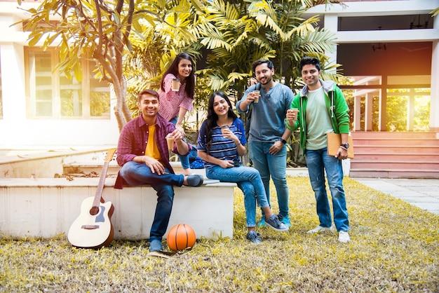 Aziatische indiase groep studenten die samen thee of koffie drinken in de pauze op de campus in de buitenlucht. een praatje maken