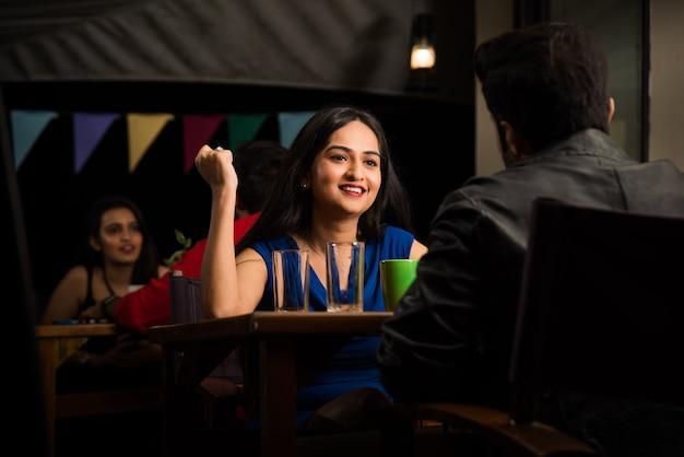 Aziatische indiase jonge indiase mensen die 's avonds in restaurant eten?