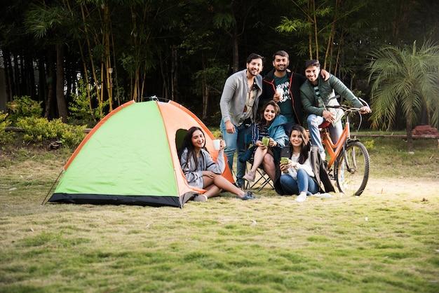 Aziatische indiase jonge vrienden hebben veel plezier op een kampeertrip, een ontspannende vakantie met leuke buitententen