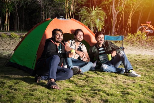 Aziatische indiase jonge vrienden hebben veel plezier op een ontspannende vakantie op de camping met plezier buiten tenten
