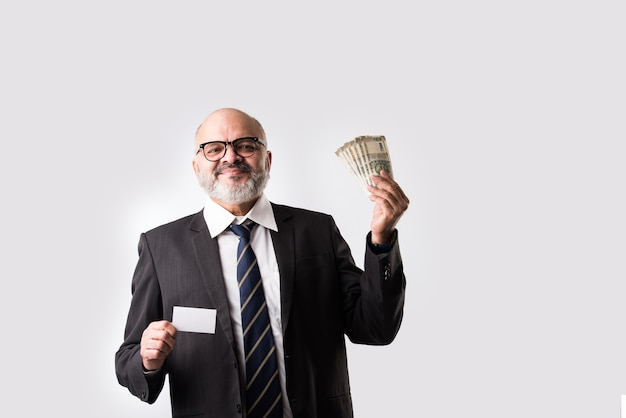 Aziatische indiase oude zakenman met bankbiljetten, geldventilator, lege elektronische debetcreditcard
