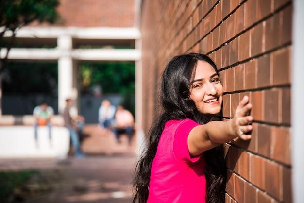 Aziatische indiase student in focus die op laptop werkt of een boek leest terwijl andere klasgenoten op de achtergrond, buitenfoto op de universiteitscampus