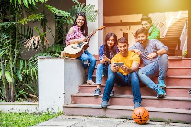 Aziatische indiase studenten die muziek spelen met gitaar terwijl ze op de campus op trappen of over gazon zitten