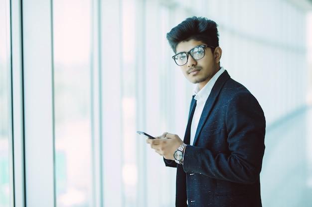 Aziatische indische bedrijfsmensen die gebruikend smartphone texting terwijl het lopen in modern bureau